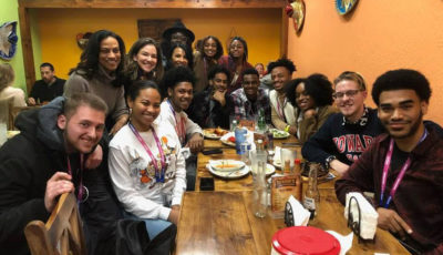 Howard University hopeful apprentices are gathered around a table at a Mexican restaurant smiling.