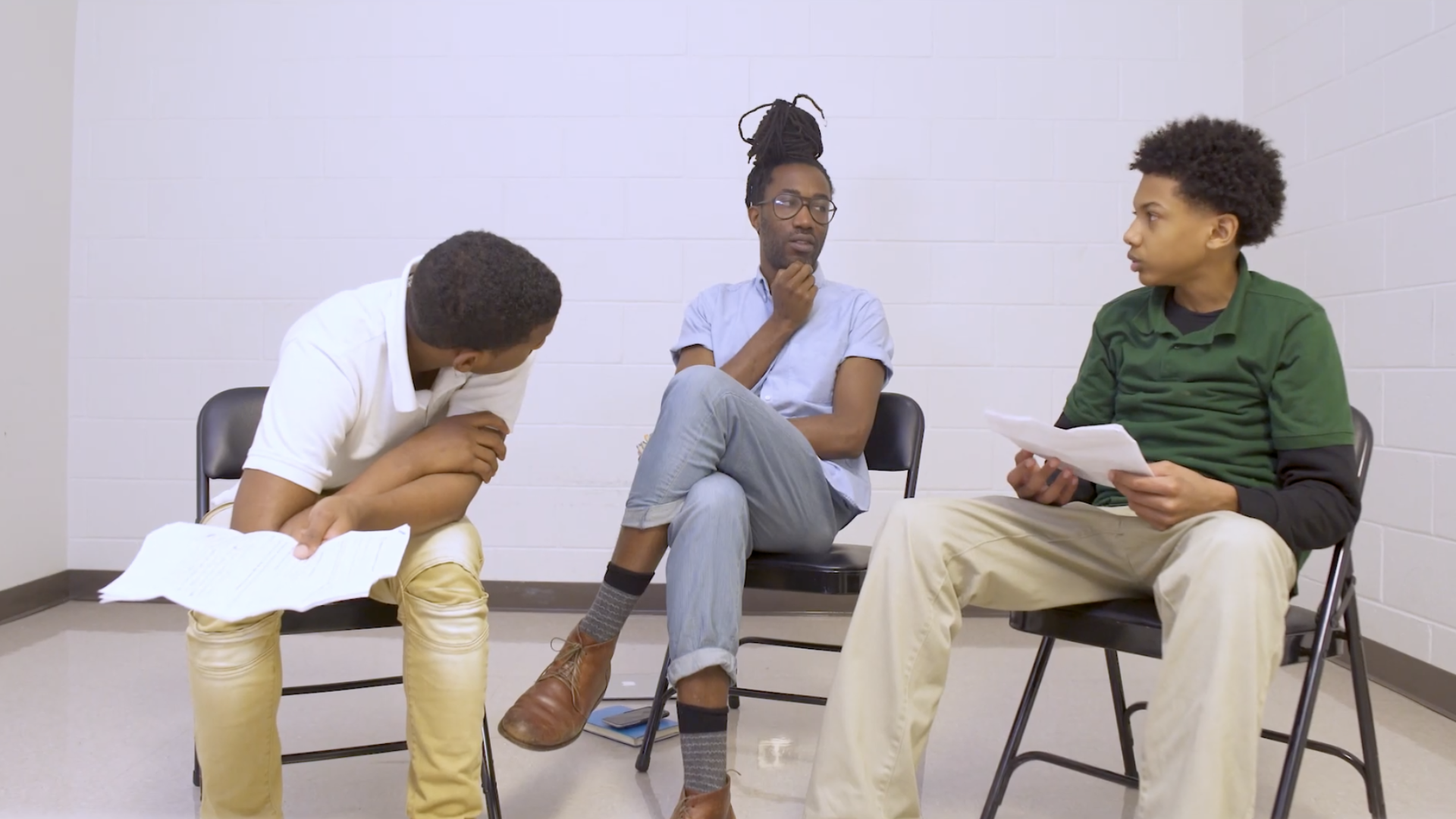 Black male instructor with a bun, listening to two black teens holding scripts