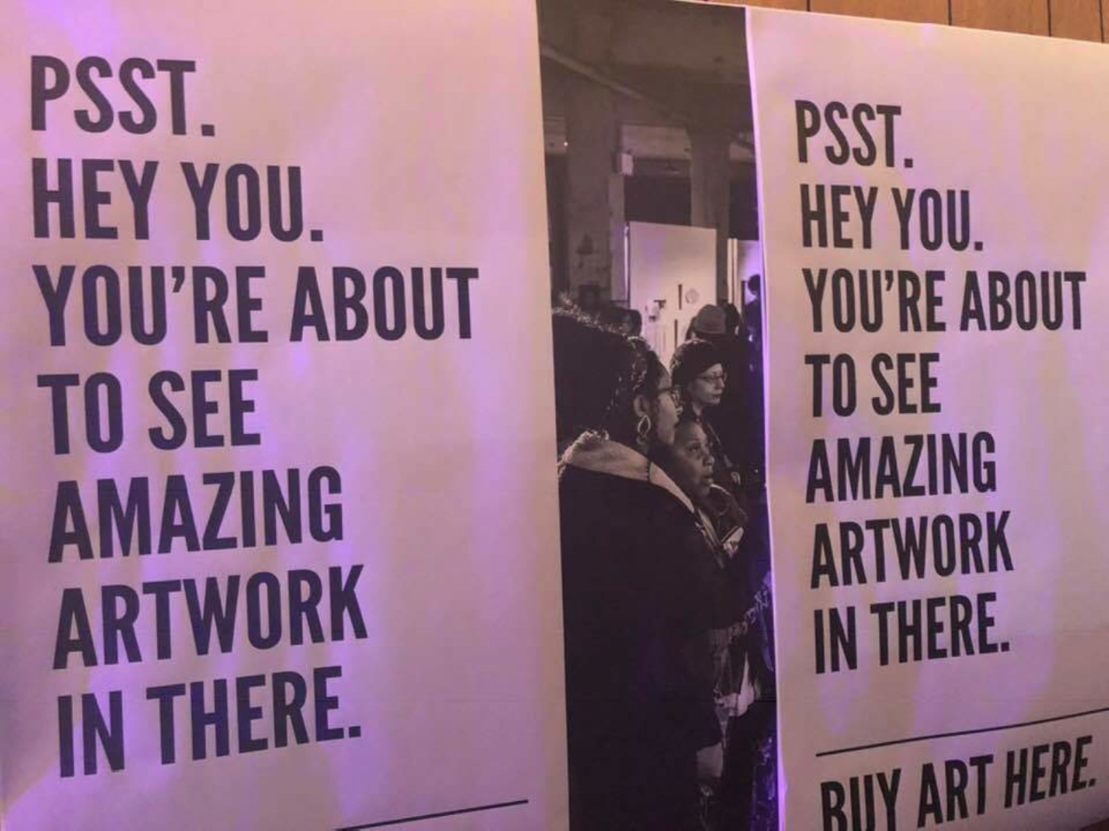 "Sign at an art show says, ""You're about to see amazing artwork in there."" In the background is a gallery room full of people."